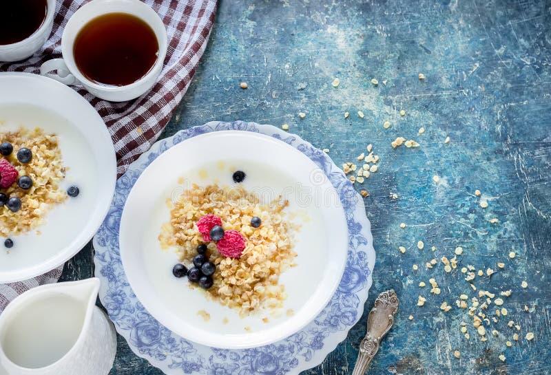 Gezond ontbijt: havermeelvlokken met bessen en thee/koffie stock foto