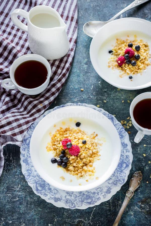 Gezond ontbijt: havermeelvlokken met bessen en thee/koffie royalty-vrije stock afbeeldingen