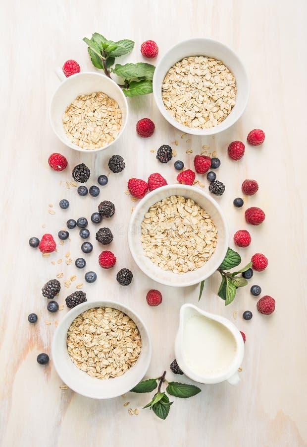 Gezond ontbijt: havervlokken in kommen, verse bessen en melk op witte houten achtergrond royalty-vrije stock afbeeldingen