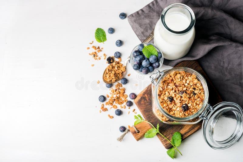 Gezond ontbijt ingrediens Eigengemaakte granola in open glaskruik, melk of yoghurtfles, bosbessen en munt stock foto's