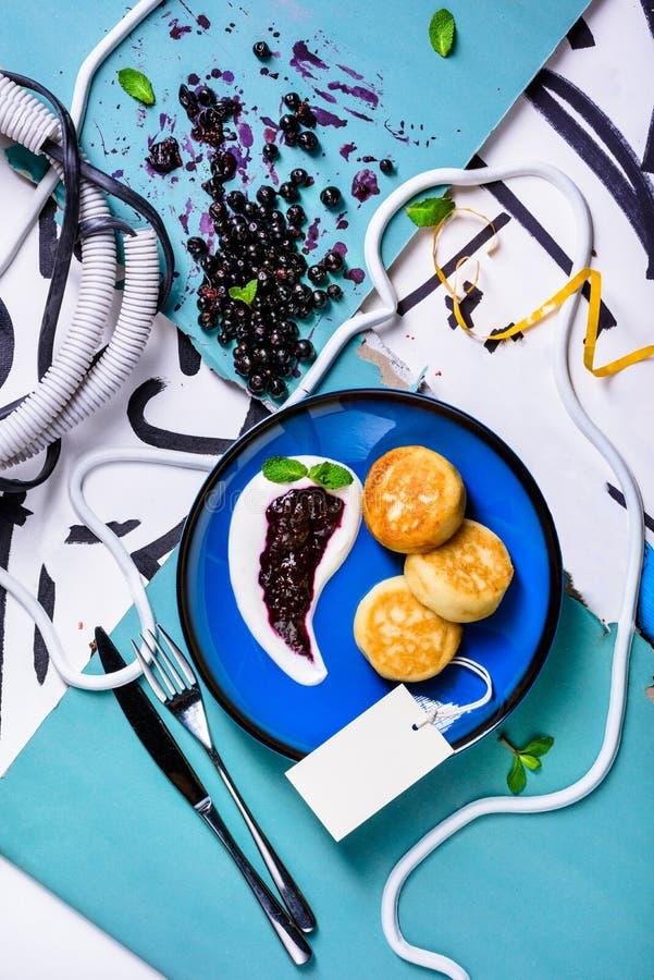 Gezond ontbijt, kwarkpannekoeken met zure room en verse bessen stock afbeeldingen