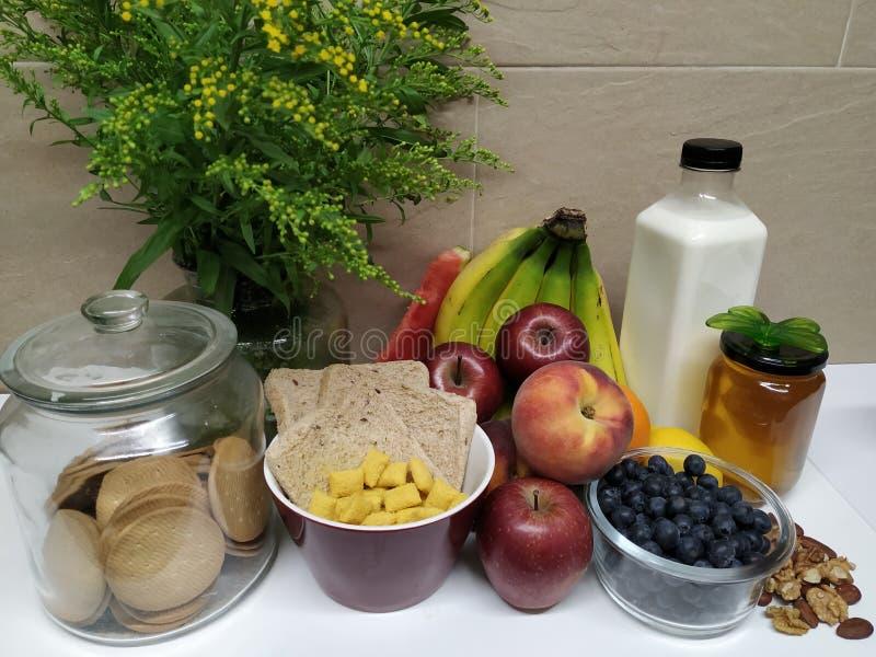 Gezond ontbijt met assortiment van vruchten en bloemen stock afbeeldingen