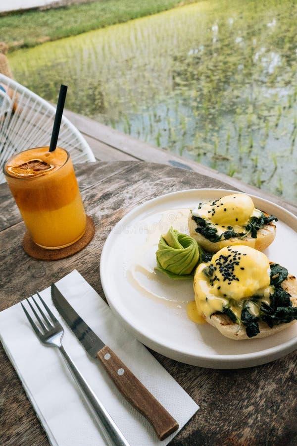 Gezond Ontbijt met Broodtoost en Gestroopt Ei met spinazie, avocado op houten lijst Sinaasappel smoothie op stock foto's