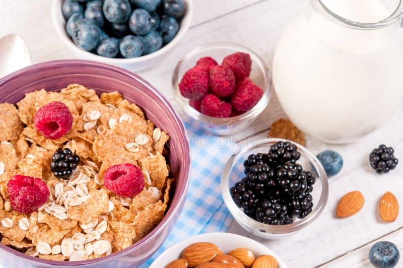Gezond ontbijt met cornflakesbessen, melk en amandelnoten op houten lijst royalty-vrije stock foto