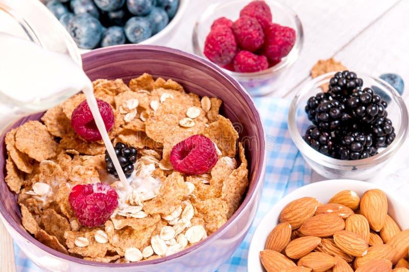 Gezond ontbijt met cornflakesbessen, melk en amandelnoten op houten lijst royalty-vrije stock afbeelding