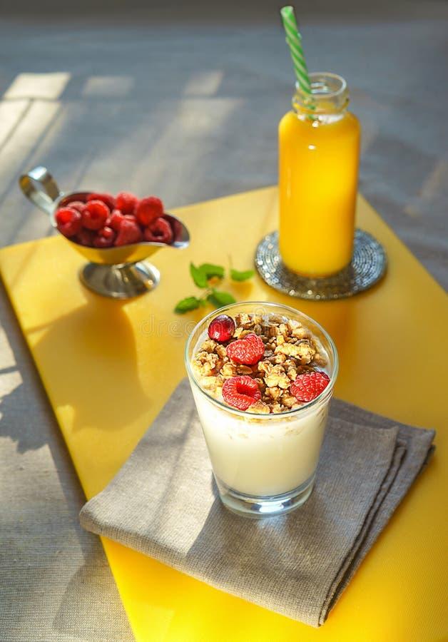 Gezond ontbijt met glas eigengemaakte granola met yoghurt en verse bessenframbozen in de zilveren munt van het kom verse jus d'or stock foto's