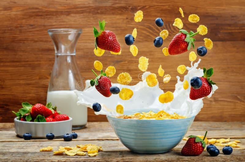 Gezond ontbijt met melk, vliegende cornflakes, aardbeien stock afbeelding