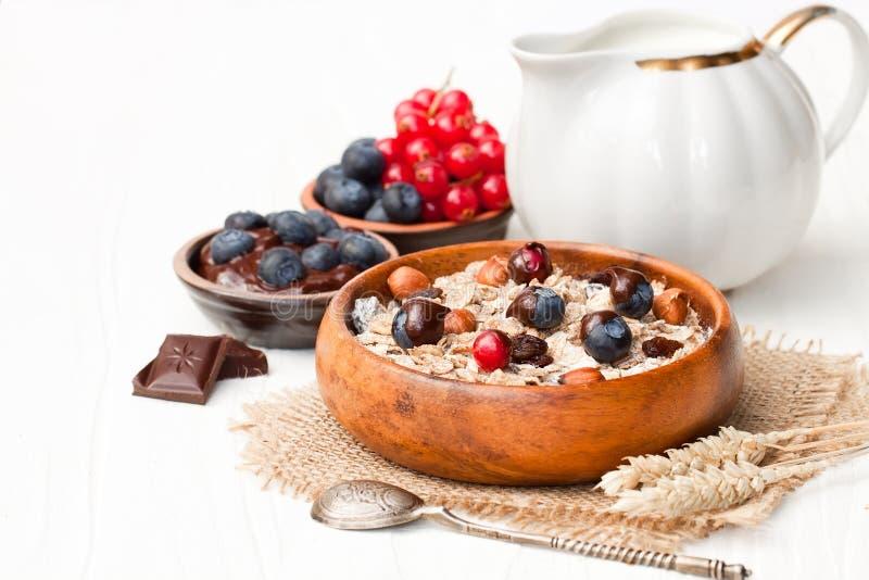 Gezond ontbijt met muesli en chocolade behandelde bessen stock fotografie