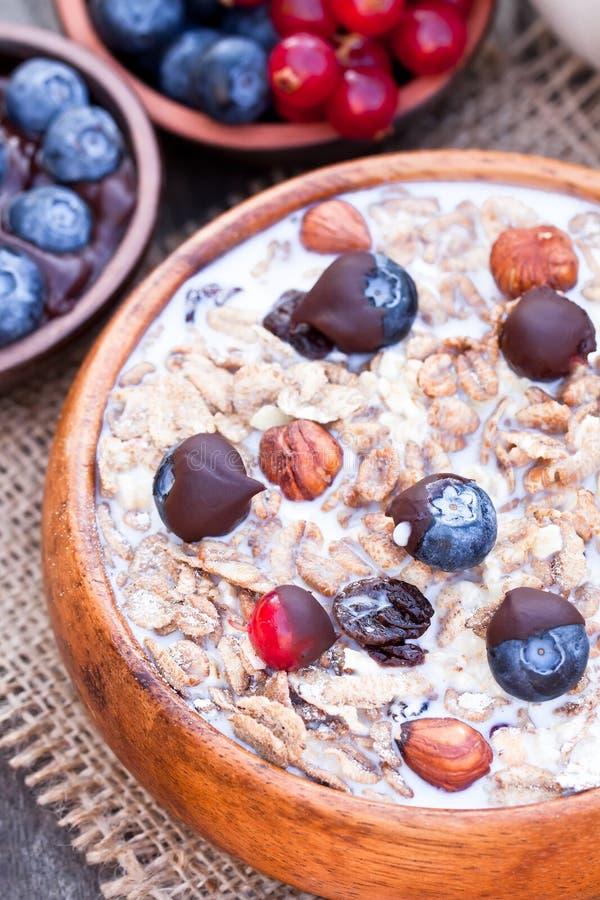 Gezond ontbijt met muesli en chocolade behandelde bessen stock foto's