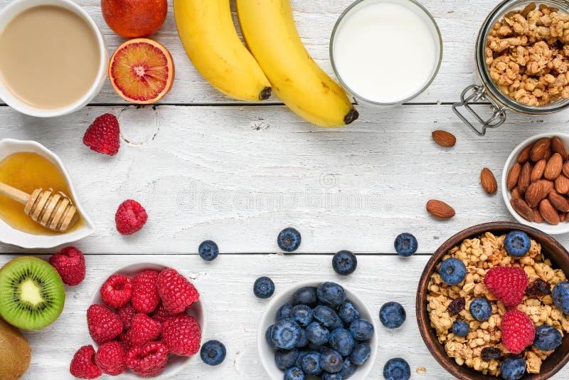 Gezond ontbijt met muesli, vruchten, bessen, cappuccino en noten op witte houten lijst royalty-vrije stock foto's
