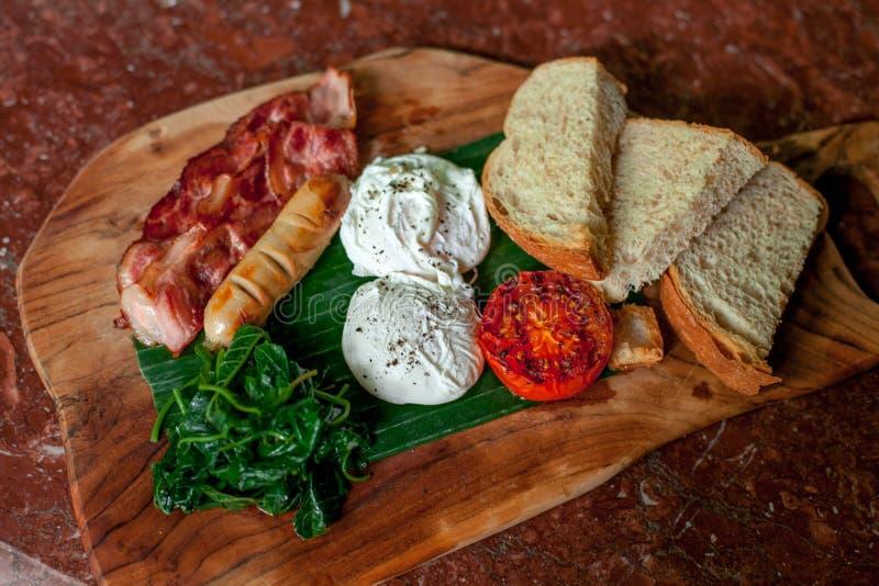 Gezond Ontbijt met Volkorenbroodtoost en Gestroopte Eieren met tomaten, bacon, worst, spinazie op de houten scherpe raad royalty-vrije stock afbeeldingen