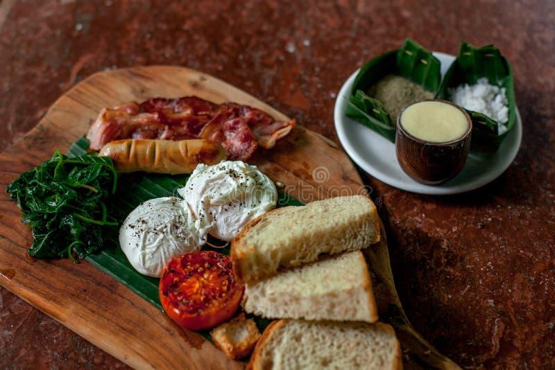Gezond Ontbijt met Volkorenbroodtoost en Gestroopte Eieren met tomaten, bacon, worst, spinazie op de houten scherpe raad royalty-vrije stock foto's