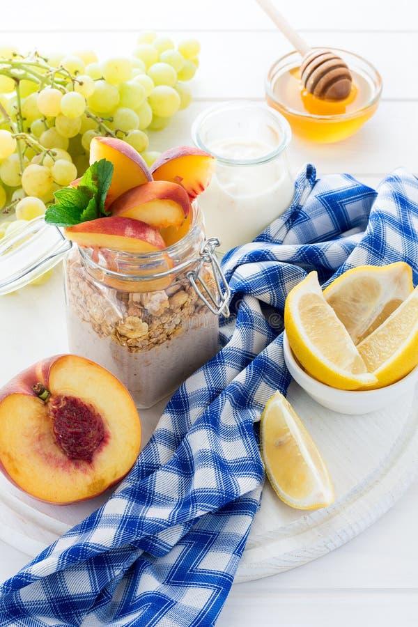 Gezond ontbijt: muesli met smoothie, honing, yoghurt en verse bessen in een glaskruik royalty-vrije stock fotografie