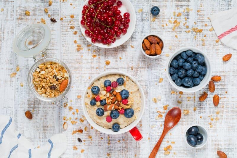 Gezond ontbijt op de lijst: havermoutpap, haver, bessen, vruchten, muesli stock foto