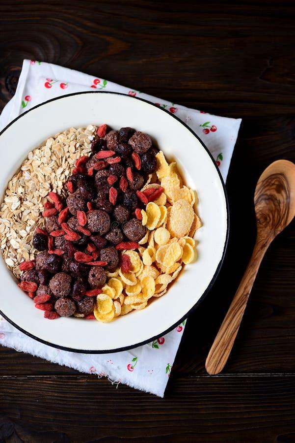 Gezond ontbijt van cornflakes, chocoladeballen, havermeel, gojibessen en verse bosbessen stock fotografie