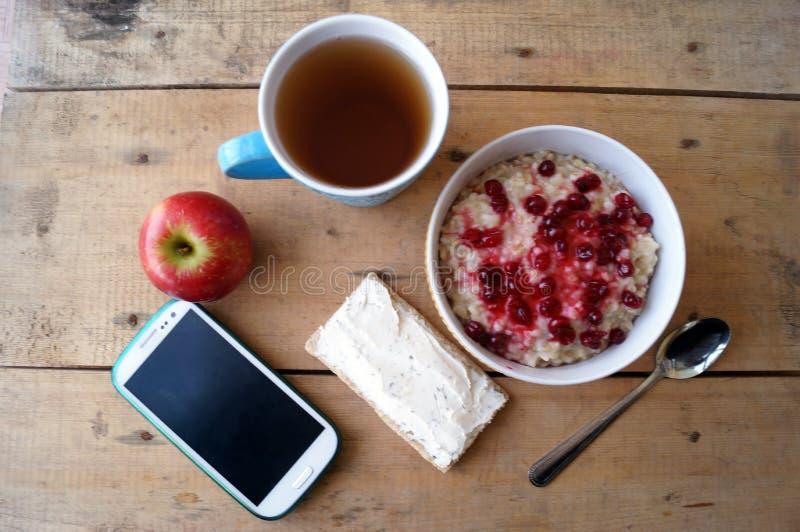 Gezond ontbijt, vegetariër Havermeel met Amerikaanse veenbessen, appel, sandwich met roomkaas, thee, mobiele telefoon stock afbeeldingen