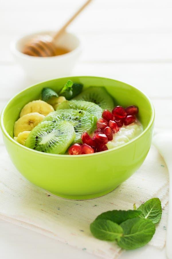 Gezond ontbijt: verse kwark met kiwi, banaan, granaatzaden en honing verfraaide muntbladeren stock fotografie
