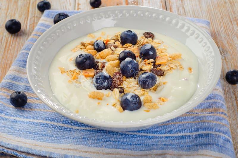 Gezond ontbijt - yoghurt met bosbessen en binnen gediende muesli royalty-vrije stock afbeeldingen