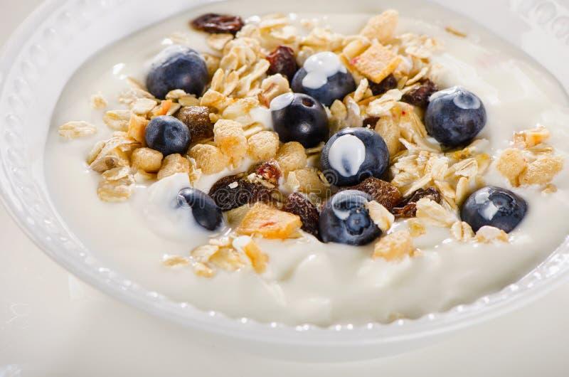 Gezond ontbijt - yoghurt met bosbessen en binnen gediende muesli stock foto's