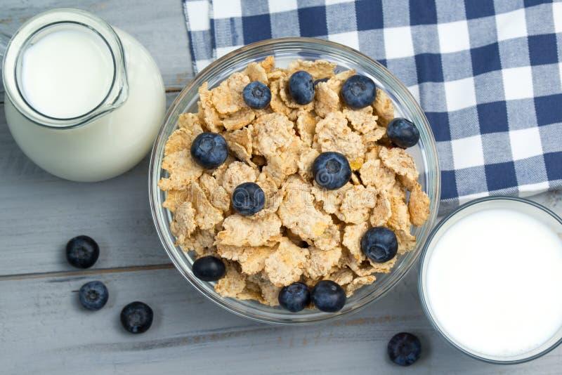 Gezond ontbijtconcept - kom graangewassen met verse bosbessen, glas en kruik melk royalty-vrije stock fotografie