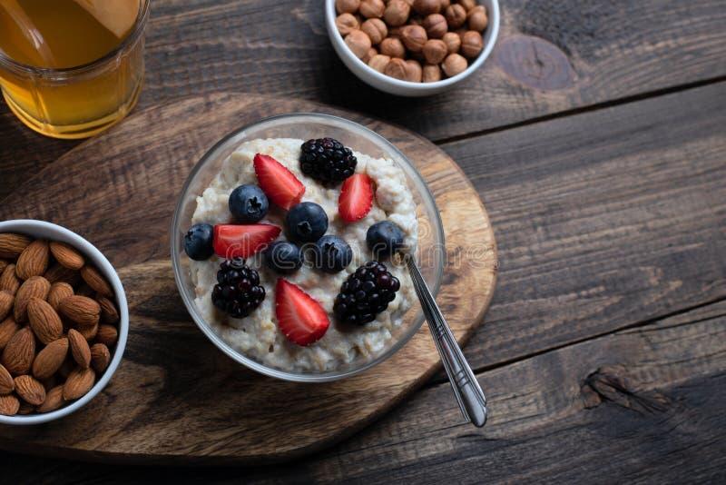 Gezond ontbijthavermeel met aardbeien, bosbessen, braambessen, amandelen en hazelnoten met gedroogd fruitcompote royalty-vrije stock afbeelding