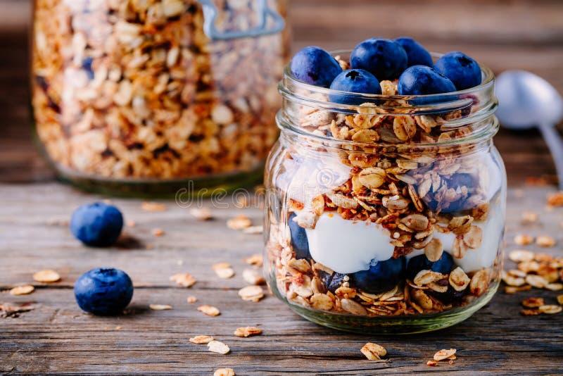 Gezond ontbijtparfait met yoghurt, eigengemaakte granola en verse bluberries in glaskruik stock foto