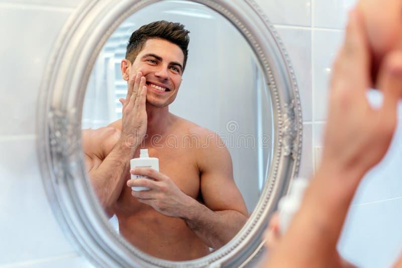 Gezond positief mannetje die het sking behandelen met lotion royalty-vrije stock foto