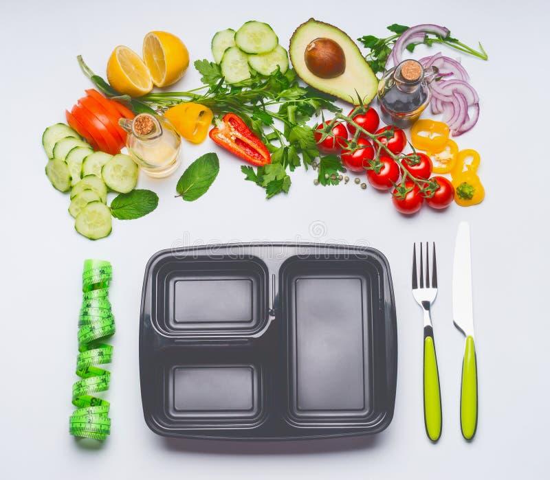 Gezond schoon het eten of dieetvoedselconcept Diverse saladegroenten met lunchdoos, bestek en groene metende band op wit royalty-vrije stock foto's