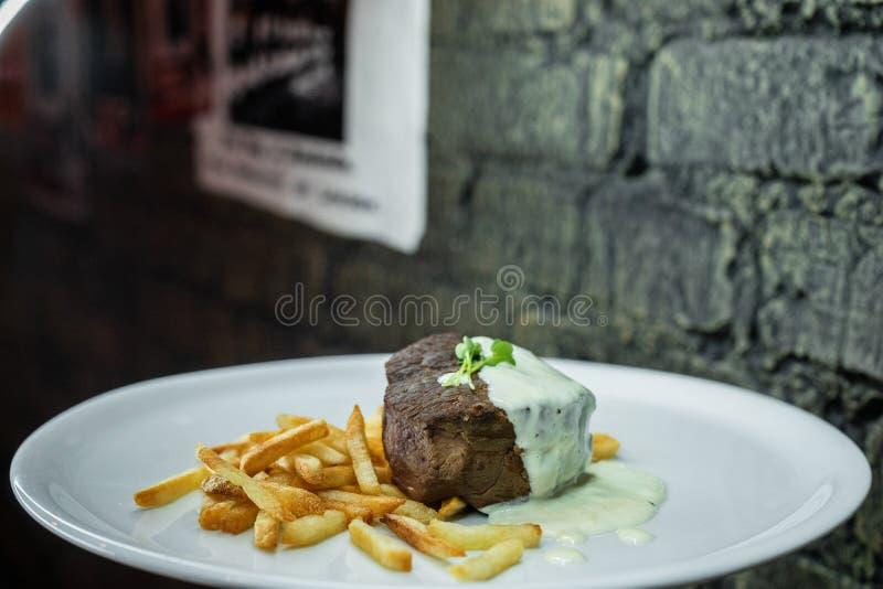 Gezond smakelijk geroosterd vlees in zure roomsaus met frieten op een witte plaat in een restaurant De tijd van het diner stock foto