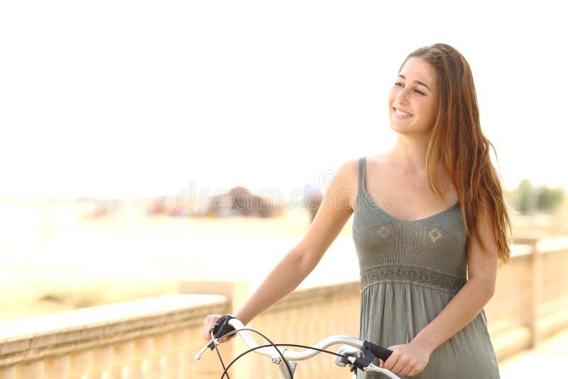 Gezond tienermeisje die met een fiets in de zomer lopen stock fotografie