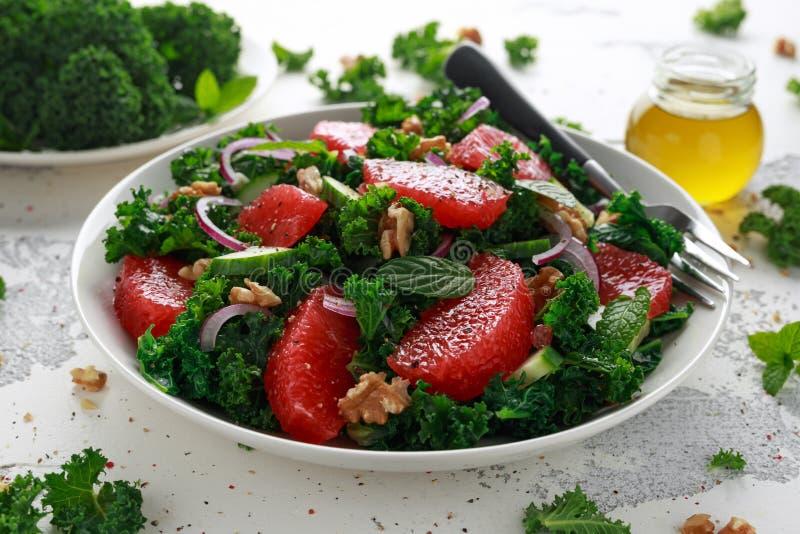 Gezond veganistvoedsel, de vegetarische salade van de Grapefruitboerenkool met okkernoten, rode ui en komkommer stock foto's
