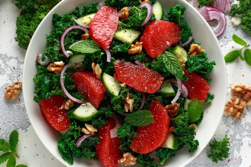 Gezond veganistvoedsel, de vegetarische salade van de Grapefruitboerenkool met okkernoten, rode ui en komkommer stock fotografie