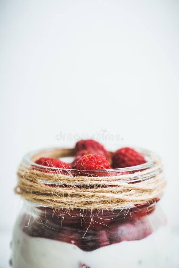 Gezond verfrissingontbijt met yoghurt, bevroren framboos en chiazaden stock foto