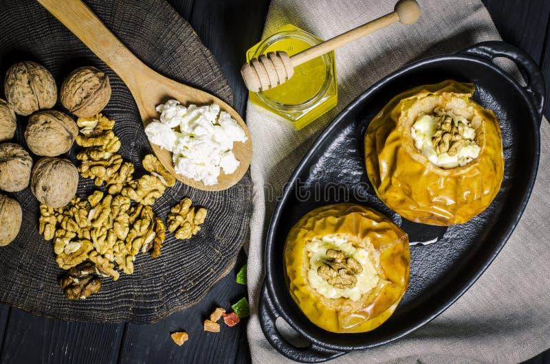 Gezond voedsel De gebakken appelen met kwark en de noten liggen in een zwarte bakselschotel op een zwarte houten lijst royalty-vrije stock afbeelding
