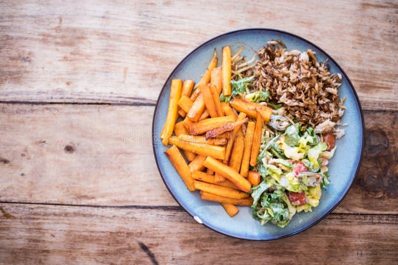 Gezond voedsel, diner voor vegetariër - de honing verglaasde wortelen, groene salade en basmati rijst royalty-vrije stock fotografie