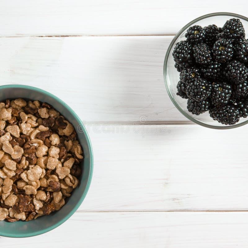 Gezond voedsel: een gezond ontbijt van cornflakes en braambessenbessen op een witte boomlijst royalty-vrije stock afbeeldingen