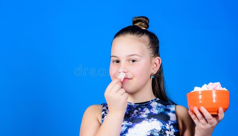 Gezond voedsel en tandzorg Het kleine meisje eet heemst Heemst De Suikergoedwinkel de gelukkige snoepjes van weinig kindliefde en stock fotografie