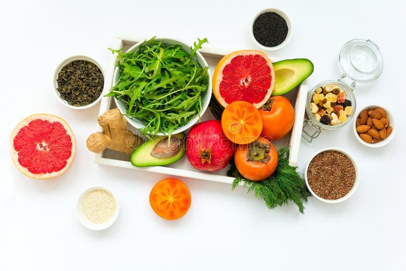 Gezond voedsel in houten dienblad: vruchten, groenten, zaden en greens op witte achtergrond stock afbeelding