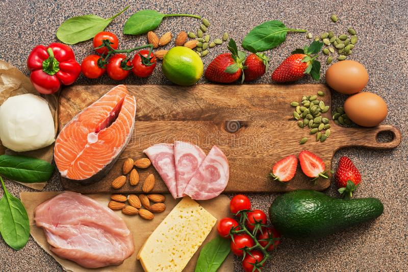 Gezond voedsel laag in koolhydraten Keto dieetconcept Zalm, kip, groenten, aardbeien, noten, eieren en tomaten, het snijden stock fotografie