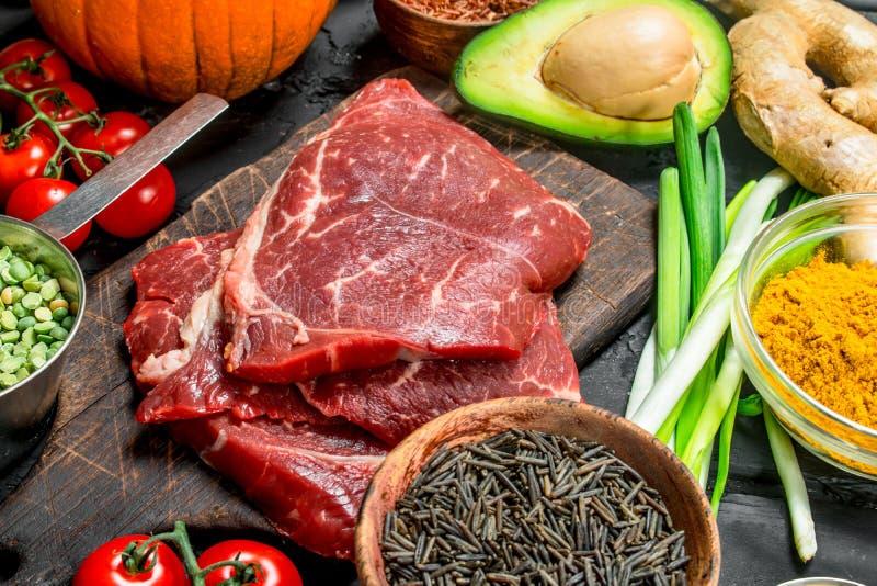 Gezond voedsel Natuurvoedingassortiment met ruwe rundvleeslapjes vlees stock afbeelding