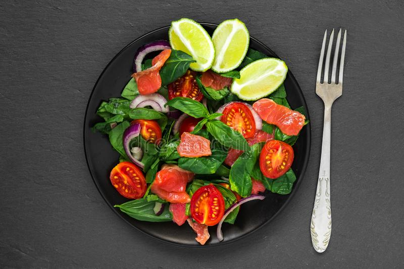 Gezond voedsel salade met zalm, spinazie, kersentomaten, rode ui, kalk en basilicum in zwarte plaat met vork stock foto's