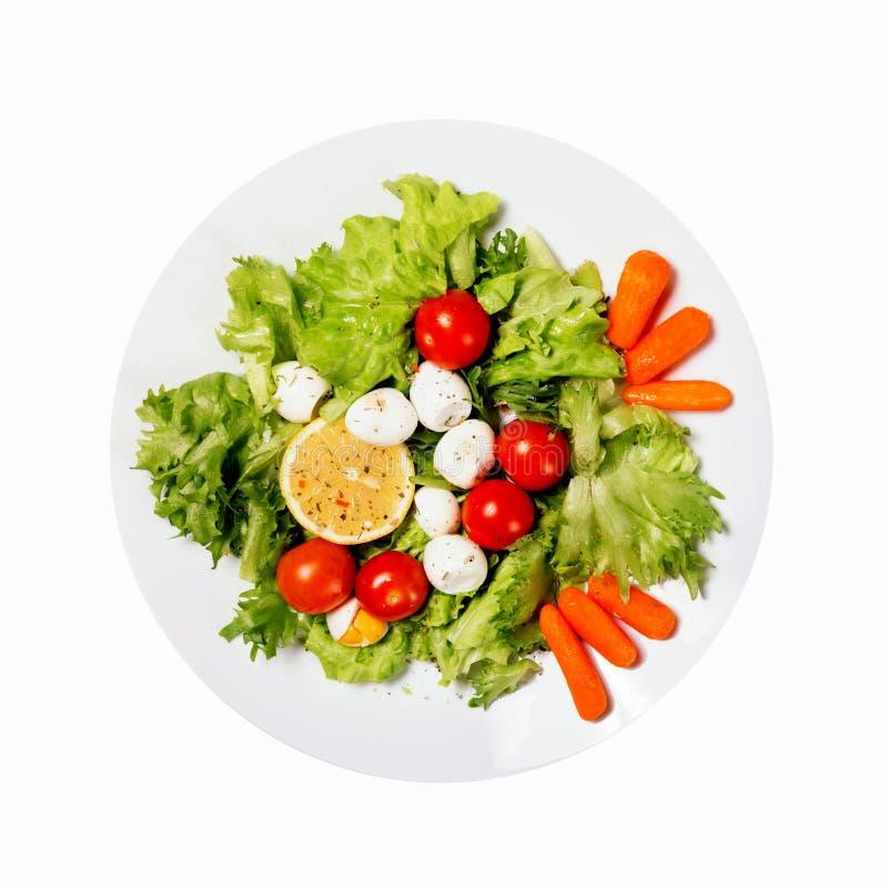 Gezond voedsel Smakelijke salade met kersentomaten, saladebladeren, citroen, kruiden, wortel en kwartelseieren die op witte achte stock afbeeldingen