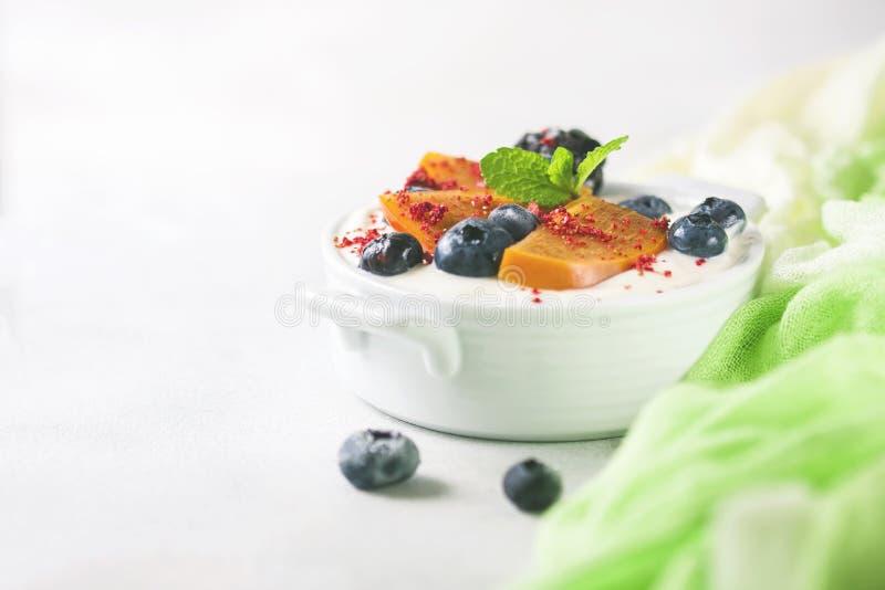 Gezond voedsel, snacks of ontbijt Eigengemaakte Griekse yoghurt met bosbessen, braambessen, dadelpruimen en munt Op a royalty-vrije stock fotografie