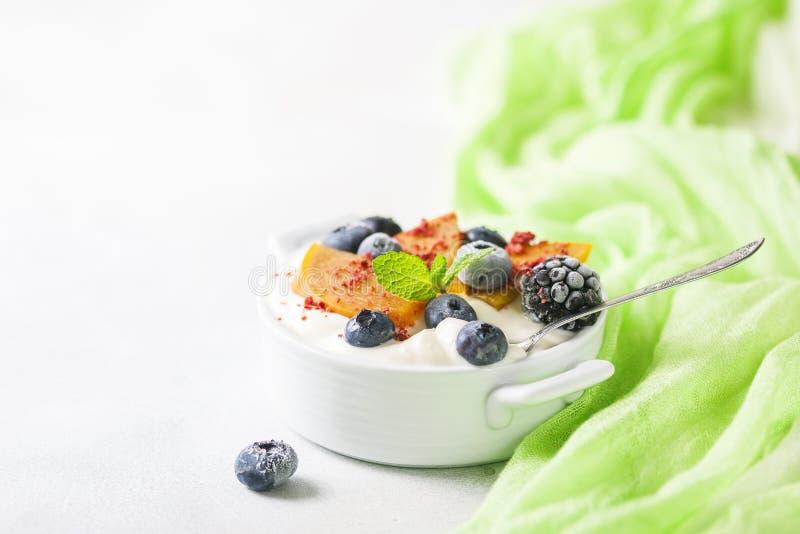 Gezond voedsel, snacks of ontbijt Eigengemaakte Griekse yoghurt met bosbessen, braambessen, dadelpruimen en munt Op a royalty-vrije stock afbeeldingen
