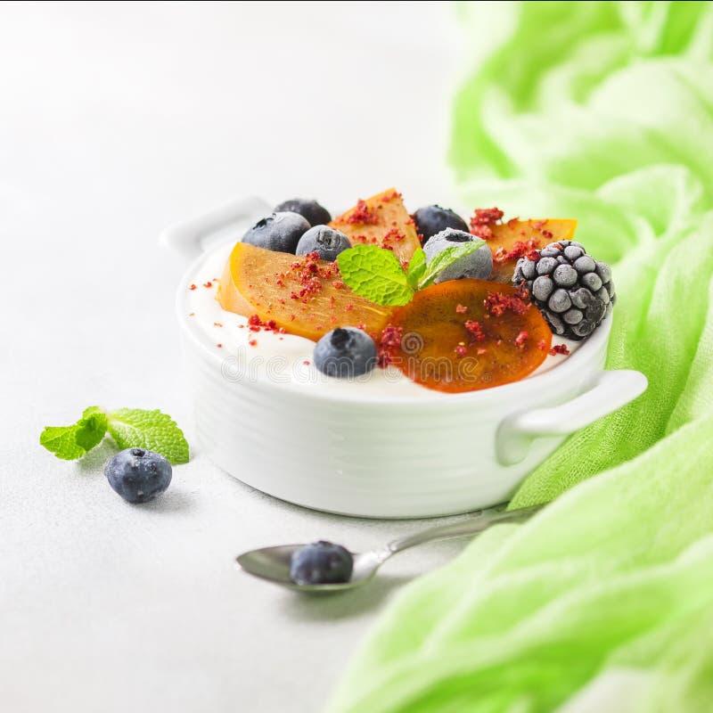 Gezond voedsel, snacks of ontbijt Eigengemaakte Griekse yoghurt met bosbessen, braambessen, dadelpruimen en munt Op a royalty-vrije stock foto's
