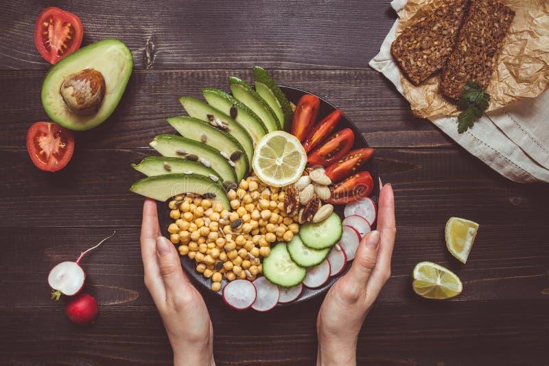 Gezond voedselconcept Handen die gezonde salade met kikkererwt en groenten houden Veganistvoedsel Vegetarisch dieet royalty-vrije stock afbeeldingen