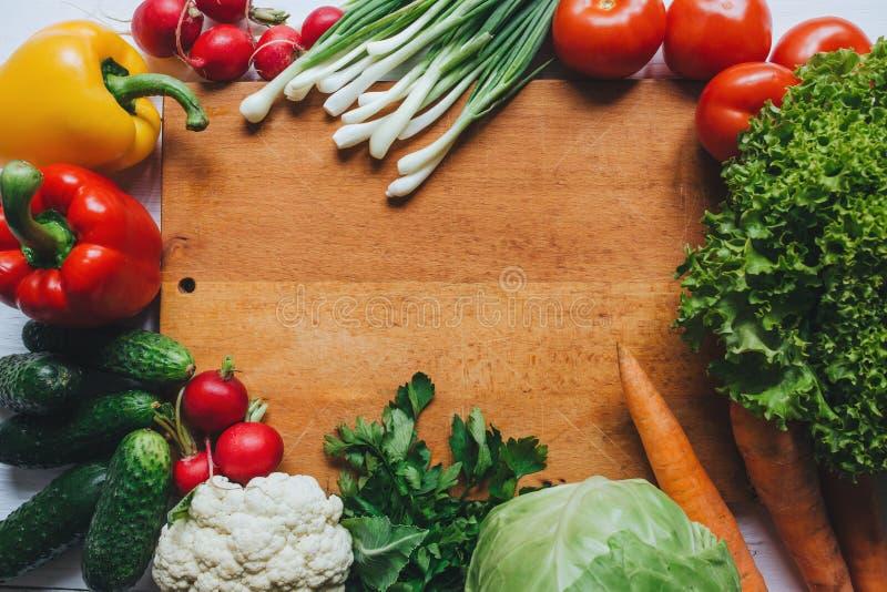 Gezond voedselconcept Het kader van de de ingrediëntengrens van de groentensalade Houten scherpe raads lege ruimteachtergrond stock afbeelding