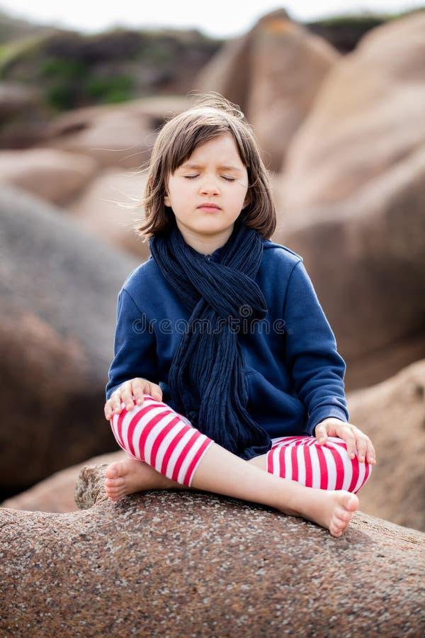 Gezond yogakind met ogen gesloten zitting in granietsteen royalty-vrije stock afbeeldingen