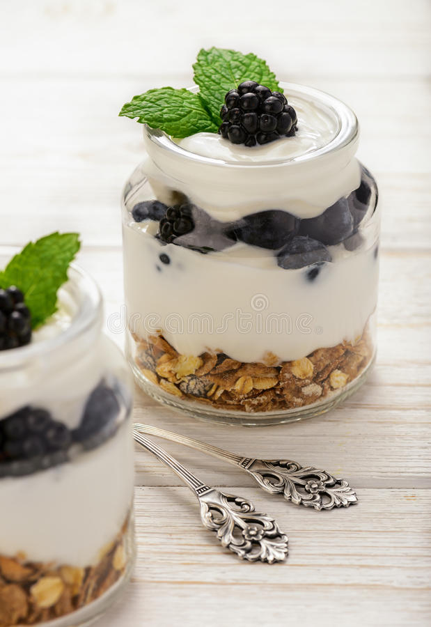 Gezond yoghurtdessert met muesli, braambessen en bosbessen op witte houten lijst stock afbeeldingen