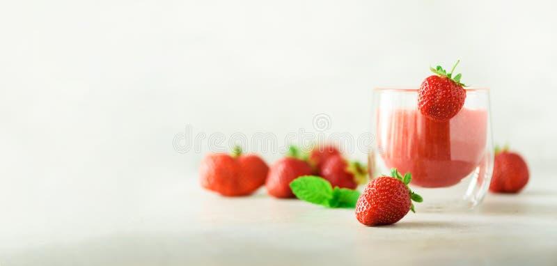 Gezonde aardbei smoothie in glas op grijze achtergrond met exemplaarruimte banner De zomervoedsel en schoon het eten concept stock foto